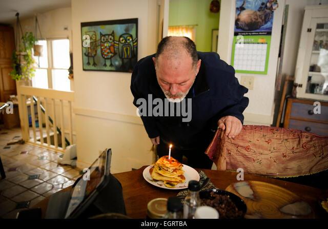 Mann in seinen 50ern Ausblasen der Kerzen auf Geburtstag Pfannkuchen an seinem Geburtstag Stockbild