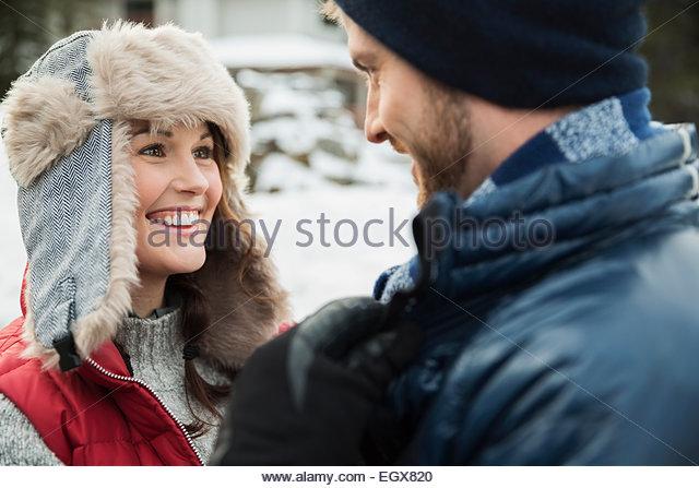 Paar in warme Kleidung lächelnd von Angesicht zu Angesicht Stockbild