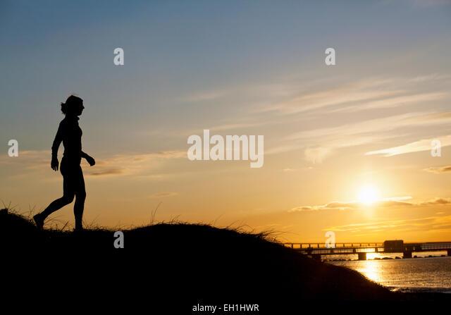 Gesamte Länge der Silhouette weibliche Läufer auf Hügel bei Sonnenuntergang Stockbild