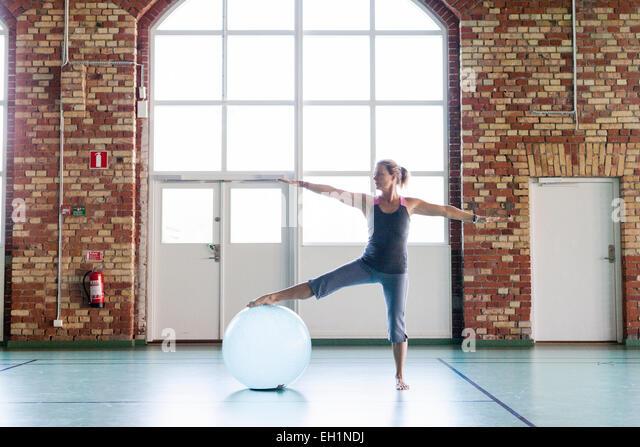 Voller Länge Frau Training mit Fitness-Ball im Health club Stockbild