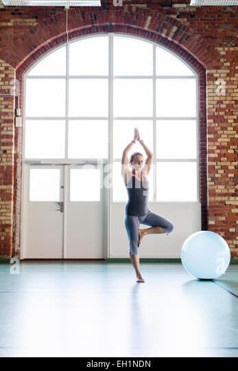 Gesamte Länge der Frau in Baum-Position im Health club Stockbild