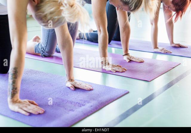 Frauen, die auf Yoga-Matten im Health Club trainieren Stockbild