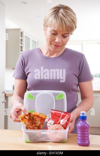 Frau Vorbereitung ungesunde Lunchbox In Küche Stockbild
