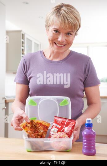Mutter bereitet ungesunde Lunchbox In Küche Stockbild