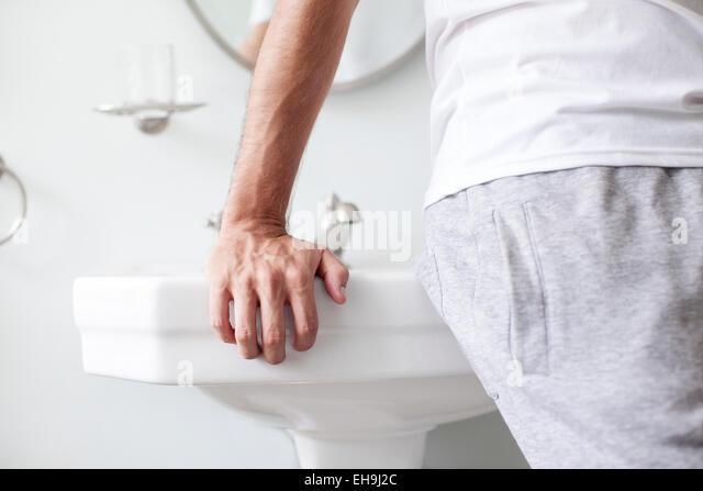 Mann gelehnt Waschbecken im Badezimmer Stockbild