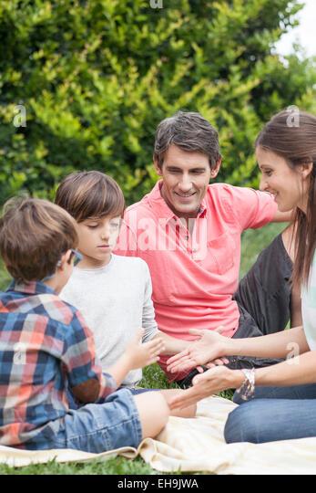 Familie Hand gemeinsames spielen bei Picknick Stockbild