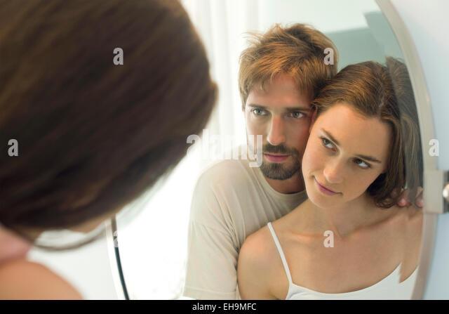 Paar Wange an Wange, einander im Spiegel zu betrachten Stockbild