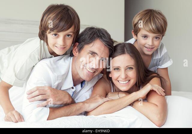 Familie auf Bett, Porträt - Stock-Bilder