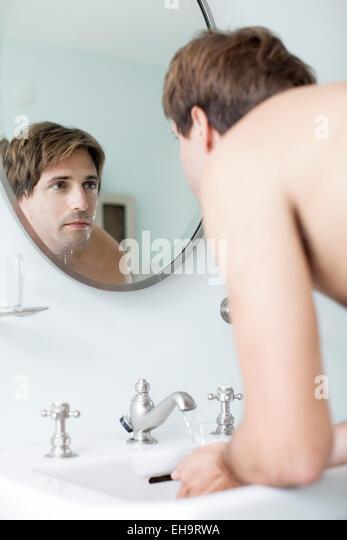 Mann waschen Gesicht im Waschbecken im Bad selbst im Spiegel betrachten Stockbild