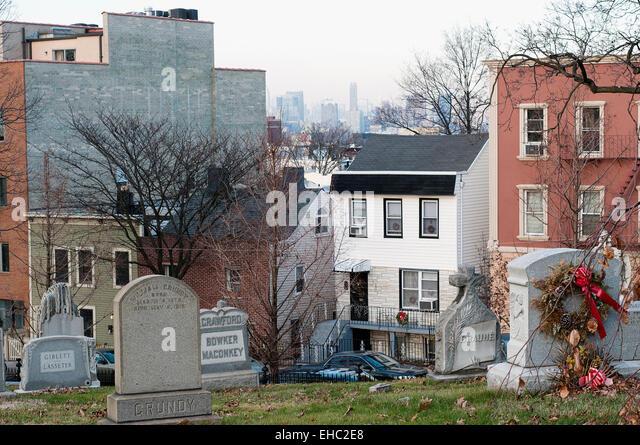 Die Häuser säumen den Rand des Green-Wood Cemetery in Brooklyn, New York. Manhattan ist im Hintergrund Stockbild
