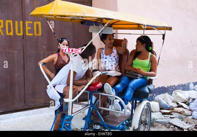 Junge Kubaner lounge auf ein Fahrrad-Taxi, Havanna, Kuba Stockbild