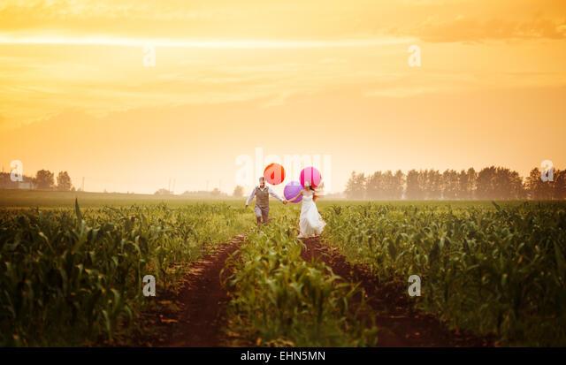 Glückliche junge Brautpaar läuft auf den Sonnenuntergang Feld mit großen hellen bunten Luftballons Stockbild