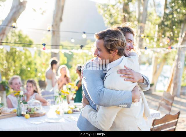 Bräutigam und Trauzeugen während der Hochzeitsfeier im heimischen Garten umarmen Stockbild