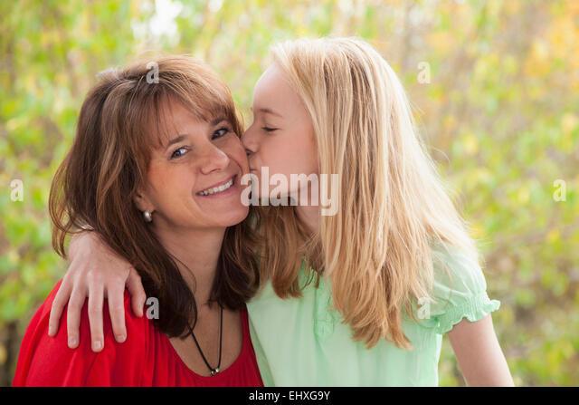Mädchen küssen ihrer Mutter, Bayern, Deutschland Stockbild