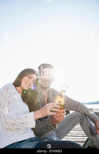 Junge Frau sitzt Steg Bier trinken Stockbild