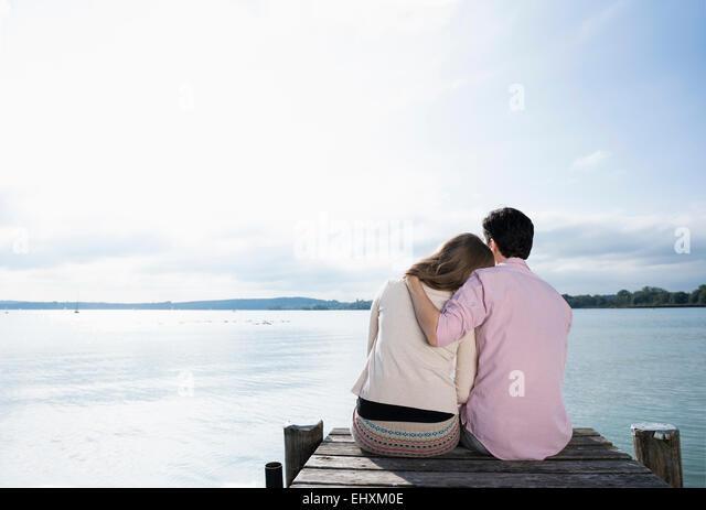 Romantisches Paar umarmt ruhigen See Steg Stockbild
