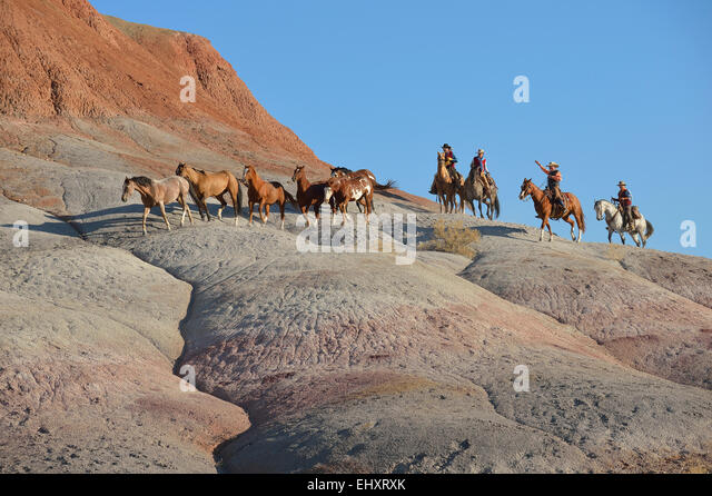 USA, Wyoming, Cowboys und Cowgirls herding Pferde in badlands Stockbild