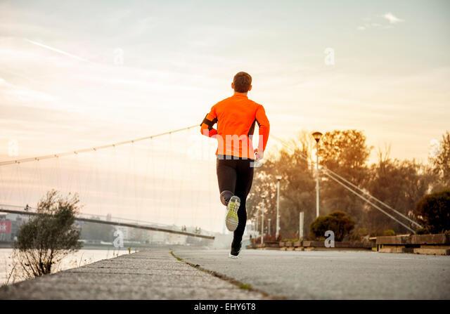 Mann mit Kopfhörer Joggen am Wasser Stockbild