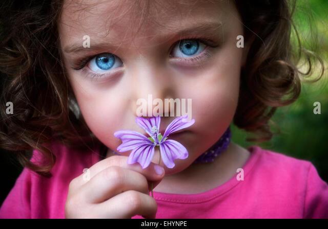 Mädchen, die eine Blume vor ihr Gesicht Stockbild