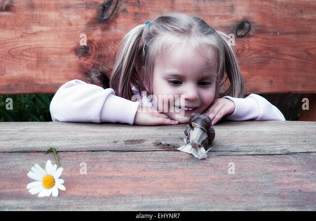 Mädchen auf der Suche auf eine Schnecke Stockbild