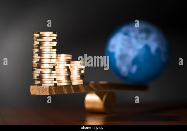 Eine Wippe mit Stapeln von Münzen auf der einen Seite und auf der anderen Seite der Erde. Stockbild