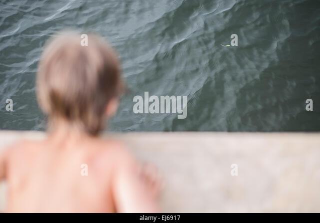 Kleiner Junge Gerben auf Holzdeck am See an heißen Sommertag. Spaß im Urlaub. Stockbild
