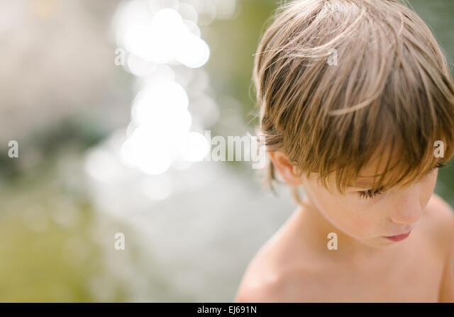 Ernsthafte niedlichen kleinen Jungen in der Nähe von Wasser am Strand an heißen Sommertag. Spaß im Stockbild