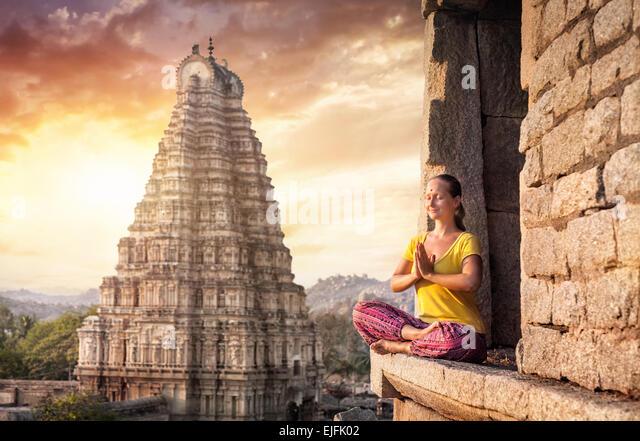 Frau mit Namaste Mudra sitzen in der Nähe von Virupaksha Tempel in Hampi, Karnataka, Indien Stockbild