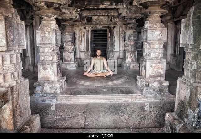 Mann tut Meditation in antiken Tempel mit carving Spalten in Hampi, Karnataka, Indien Stockbild