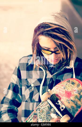 Porträt des jungen Kerl mit Skateboard und Rasta Haar selektiven Fokus in einem Lifestyle-Konzept warm Filter Stockbild