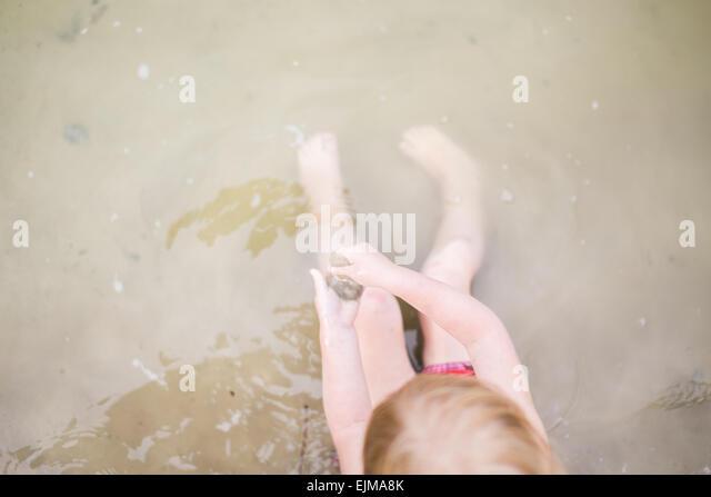 Overhead Schuss von Kleinkind Mädchen mit roten Haaren spielen im Wasser. Zeit mit der Familie am Strand am Stockbild