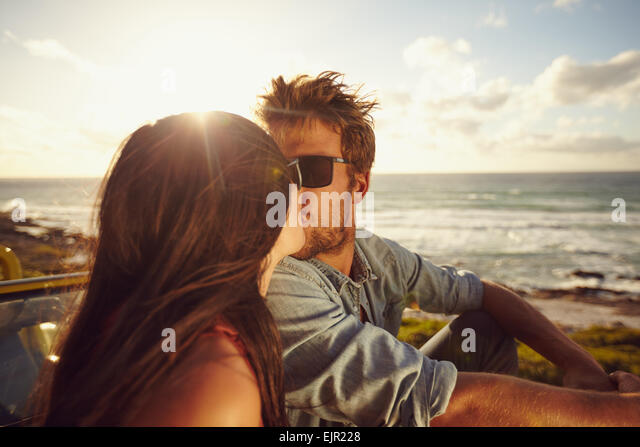 Liebevolle junge Paar küssen. Junges Liebespaar mit Meer im Hintergrund. Romantisch zu zweit im Sommerurlaub. Stockbild