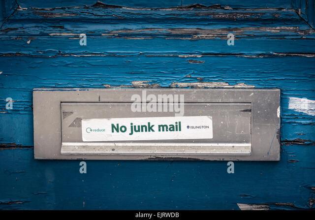 """Ein Briefkasten auf eine verwitterte Tür im Norden Londons mit einem """"No Junk-Mail""""-Aufkleber. Stockbild"""