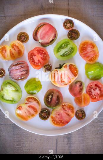 Einem weißen Teller voll von verschiedenen Größen und Farben der geschnittenen Urtomaten auf einem Stockbild