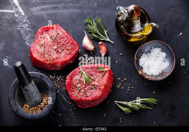Rohes frisches marmoriertes Fleisch Steak und Gewürze auf dunklem Marmor Stockbild