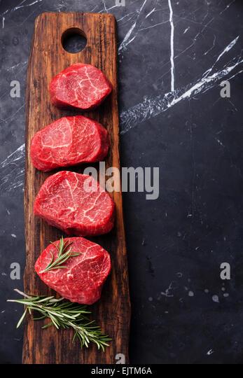 Rohes frisches marmoriertes Fleisch Steak und Rosmarin auf dunklem Marmor Stockbild
