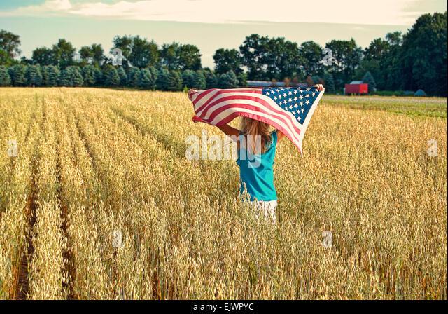 Junges Mädchen in einem Feld von Weizen mit amerikanischen Flagge. Stockbild