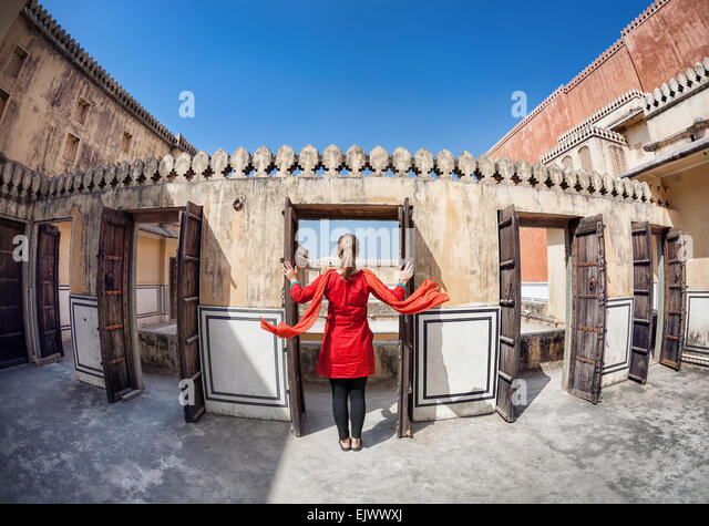 Frau im roten Kleid mit Schal Öffnen der Tür in Hawa Mahal, Rajasthan, Indien Stockbild