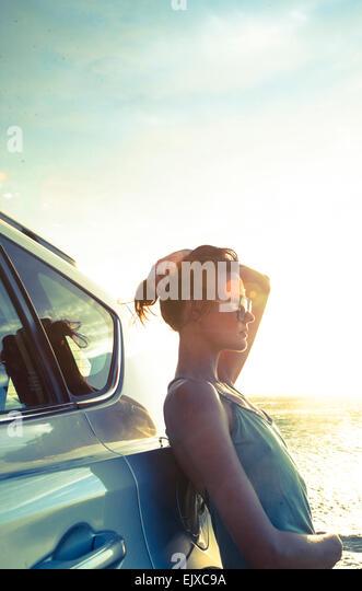 Frau gelehnt Auto bei Sonnenuntergang vom Ozean Stockbild