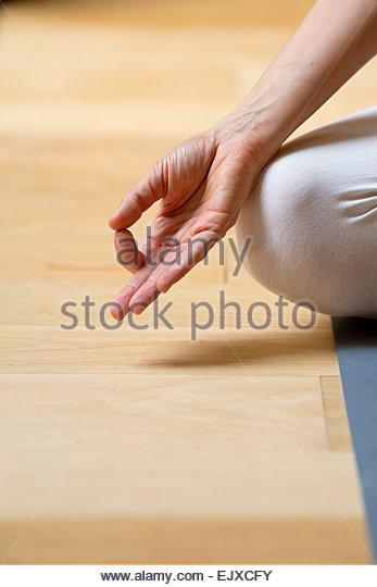 Zarte Frauenhand ruht auf Knie in Mudra Position Stockbild