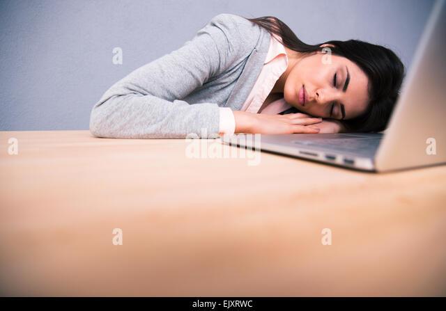Junge hübsche Frau mit Laptop auf dem Tisch schläft Stockbild