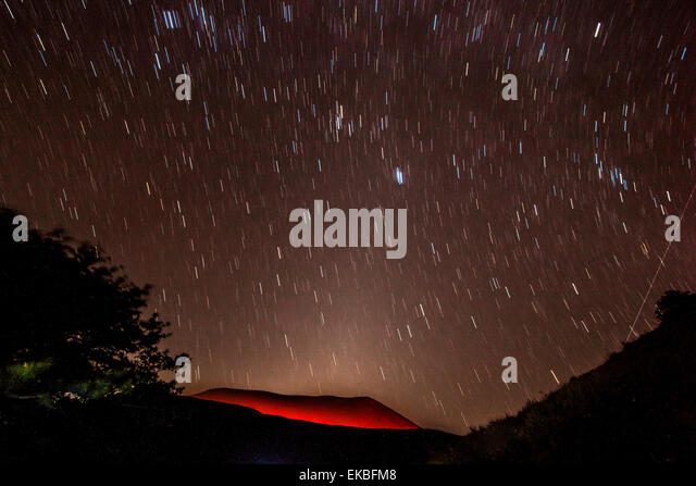 Glühende aktiven Vulkankrater des Volcan Telica nachts mit Sternspuren und Shooting Star (Meteor) rechts, Leon, Stockbild