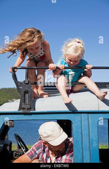 Zwei Schwestern, die auf der Suche nach unten aus dem Off Straßenfahrzeug, Lake Okareka, Neuseeland Stockbild