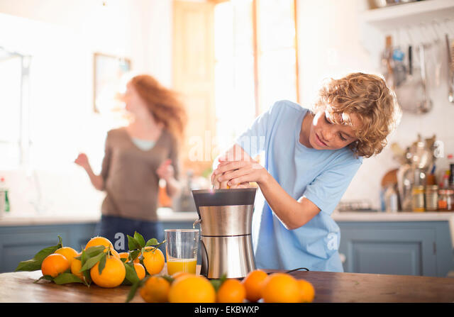 Teenager Entsaften Orange in Küche Stockbild