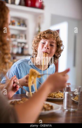 Teenager, Spaghetti-Essen am Esstisch Stockbild