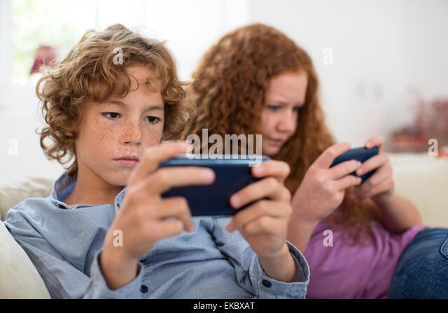 Geschwister spielen mit Handheld-Computer-Spiel auf couch Stockbild