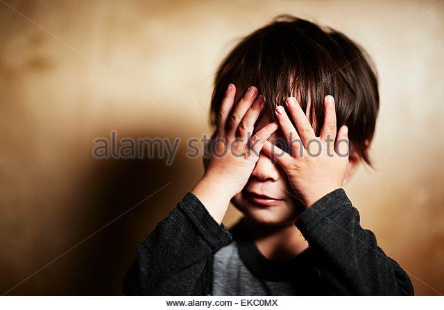 Porträt von niedlichen männliche Kleinkind spähen durch Finger Stockbild