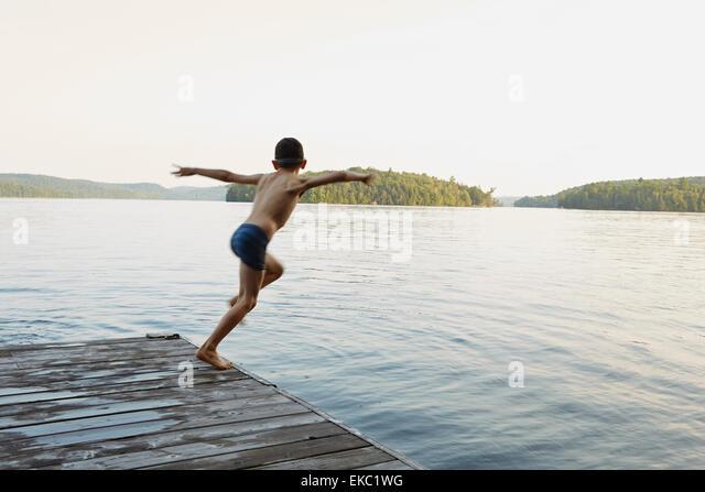 Junge, springen in See von hölzernen Pier, Ontario, Kanada Stockbild