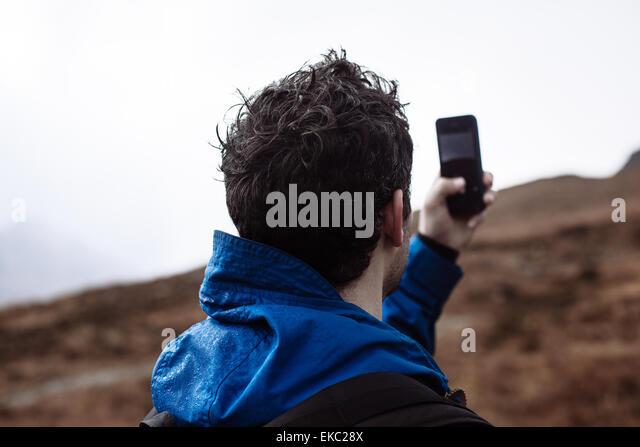 Mitte erwachsenen Mannes nehmen Foto mit Handy Stockbild