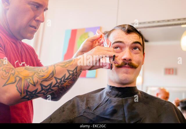 Junger Mann mit Lenker Schnurrbart mit Haare schneiden Stockbild